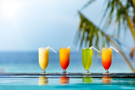 drinks on bar: Fresh summer cocktails drinks placed next to swimming pool with ocean on background.