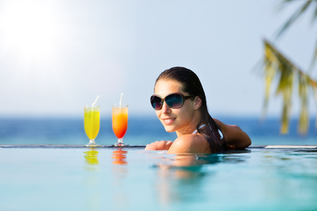 pool bar: Brunette girl with cocktails relaxing in swimming pool, ocean on background