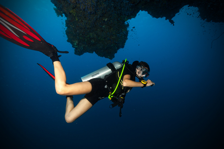 Young female scuba diver swimming underwater below reef