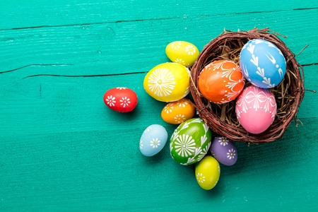 Colorful Easter eggs in basket placed on wooden planks. Copyspace for text