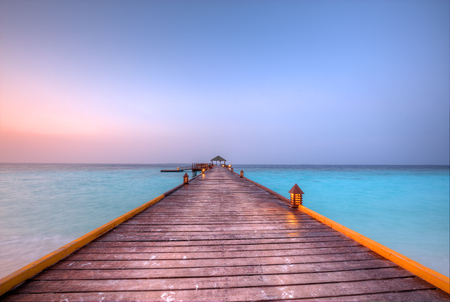 Wooden jetty in Maldives with beautiful sunset clouds