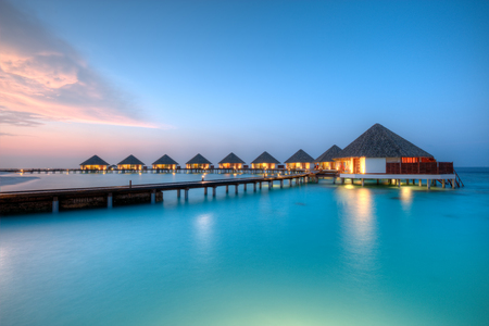 Water villas in lagon, Maldives resort island in sunset