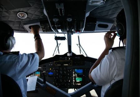 pilot cockpit: Rear view of pilot and copilot in cockpit of small private aeroplane