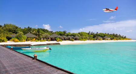 caribbean beach: Tropical island resort on Maldives with wooden jetty and sea plane Stock Photo
