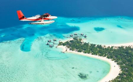luz do sol: Sea avião voando acima ilhas Maldivas, atol Raa Imagens