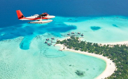 Sea plane flying above Maldives islands, Raa atol