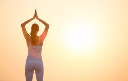 vriksasana: Young woman practising yoga in beautiful sunset