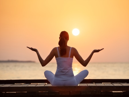 sun beach: Young woman practicing yoga on the beach at beautiful sunset Stock Photo