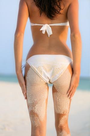 culo di donna: Giovane donna in bikini guardando spiaggia con sabbia sul suo corpo, sparato da dietro