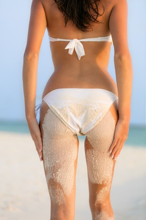 blue bikini: Young woman in bikini looking at beach with sand on her body, shot from behind