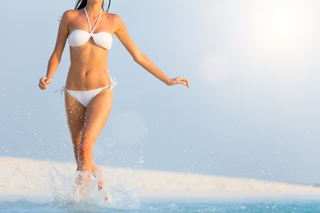 life style: Close-up of woman running on beach, concept of exercise and healthy life style. Stock Photo