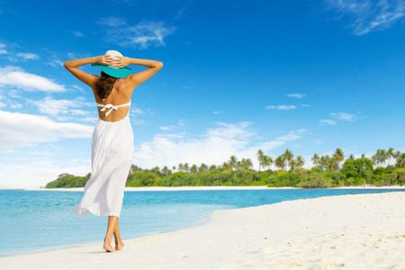 Beautiful girl walk on tropical beach. Shot from behind. Concept of happiness and vacation