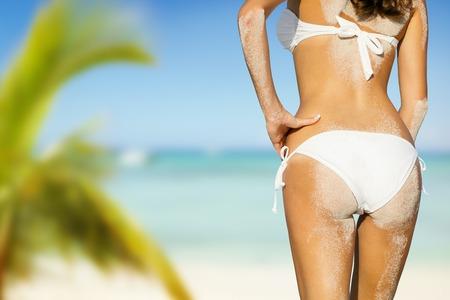 chica sexy: mujer joven en bikini en busca de playa con arena sobre su cuerpo, disparó desde atrás