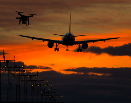 potentially: Drone potentially being hit by commercial airplane in sunset silhouettes. Concept of aircraft accident. Thread of collision