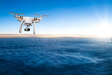 above clouds: Drone for industrial works flying above clouds. Concept of pottential danger of aircraft collision