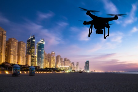 Drone silhouette flying above Dubai city panorama in sunset Stock Photo