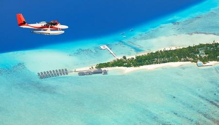 Sea plane flying above Maldives islands, Raa atol