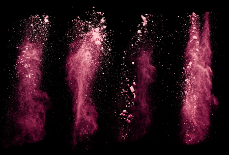 Explosion of red powders, isolated on black background