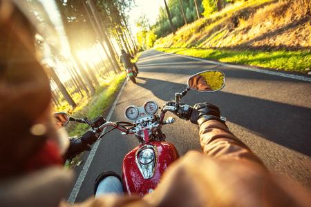 motociclista: Motociclista montar en moto por la carretera en la ma�ana d�a soleado. Disparo desde atr�s