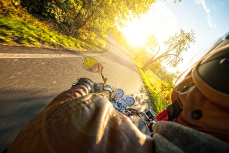 shot from behind: Motorcyclist riding motorbike  on road in morning sunny day. Shot from behind Stock Photo