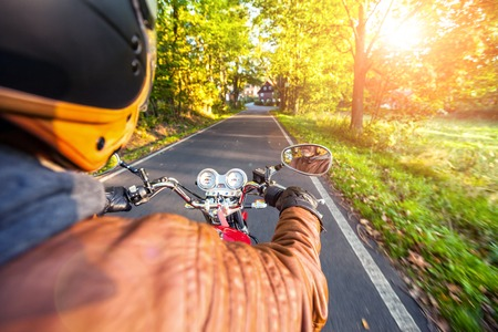 motorcyclist: Motorcyclist riding motorbike  on road in morning sunny day. Shot from behind Stock Photo