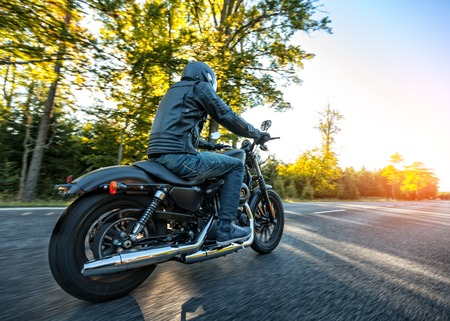 motorcyclist: Motorcyclist riding a chopper on a road in morning sun Stock Photo