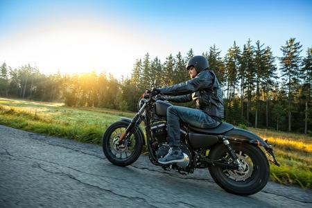 motociclista: Motociclista que monta un interruptor en un camino en el sol de la ma�ana Foto de archivo