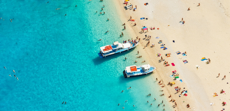 motorboats: Aerial view of a beach with motorboats and people swimming in the sea, Greece Stock Photo