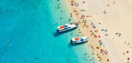 Luftaufnahme eines Strandes mit Motorbooten und Menschen schwimmen im Meer, Griechenland Standard-Bild - 53581659