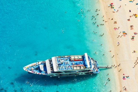 cruise travel: Aerial view of a beach with big cruise ship and people swimming in the sea, Greece