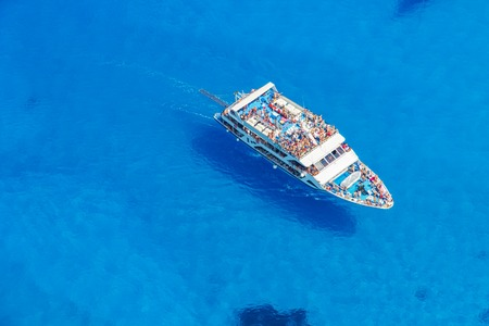 cruise travel: Aerial view of over-croaded cruise boat in azure sea, vacation and travel concept