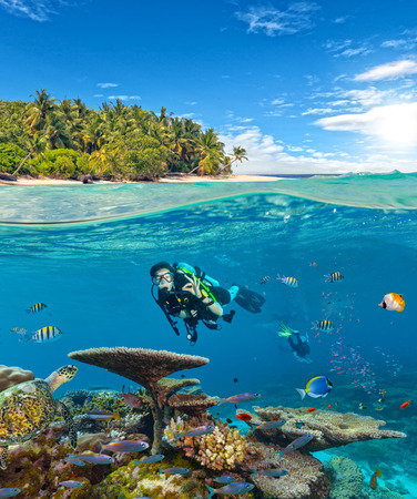 Underwater view of coral reef and scuba diver showing ok sign with horizon and water surface split by waterline. Beautiful nonsettled tropical island on background. Summer holiday concept. High Resolution