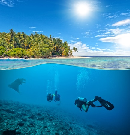 waterline: Underwater view of coral reef and scuba divers and manta ray with horizon and water surface split by waterline. Beautiful nonsettled tropical island on background. Summer holiday concept. High Resolution