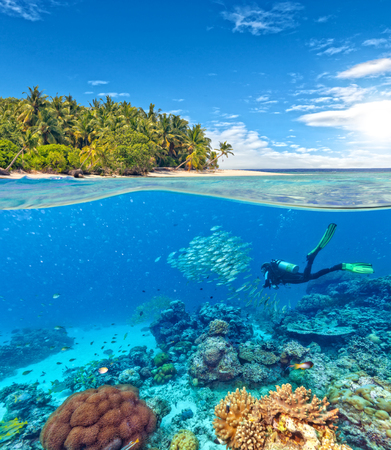 Underwater view of coral reef and scuba diver with horizon and water surface split by waterline. Beautiful nonsettled tropical island on background. Summer holiday concept. High Resolution
