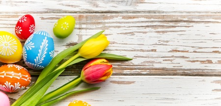 Colorful easter eggs and tulips placed on wooden background