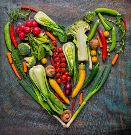 Collection of fresh green vegetables in heart shape placed on black stone