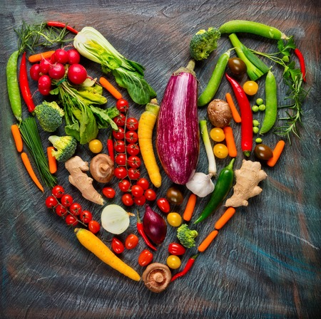 veggies: Collection of fresh green vegetables in heart shape placed on black stone