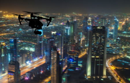 Drone silhouette flying above Dubai city panorama at night