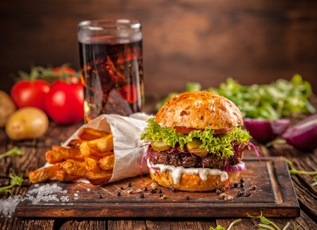pomme: Fresh home-made hamburger served on wooded table with pomme fries and cola drink Stock Photo