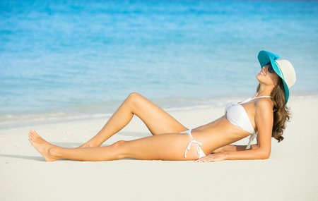 girl lying: Side view of long haired young woman in swimsuit looking at sea . Concept of relaxing and vacation
