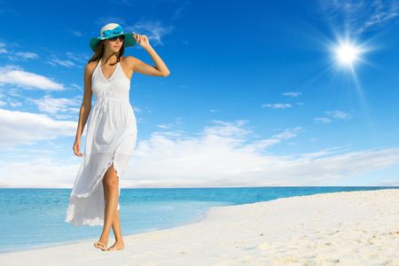 beach wear: Beautiful girl walking on tropical beach. Concept of happiness and vacation