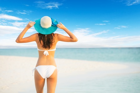 shot from behind: Beautiful girl walk on tropical beach. Shot from behind. Concept of relaxation and vacation