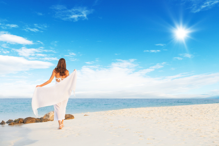 Beautiful girl walk on tropical beach. Shot from behind. Concept of relaxation and vacation