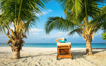 Woman relaxing on deckchair, tropical beach of Indian ocean, Maldives Stock Photo