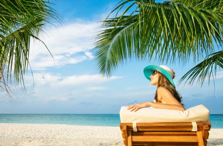 deckchair: Woman relaxing on deckchair, tropical beach of Indian ocean, Maldives Stock Photo