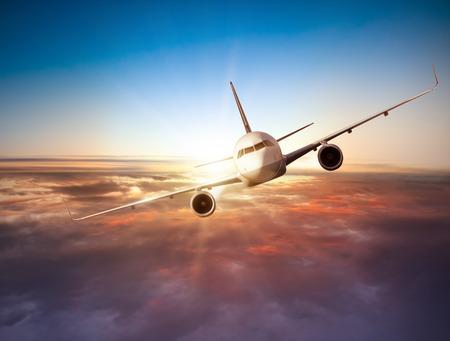 Commerciële vliegtuig vliegt boven de wolken in dramatische zonsondergang licht