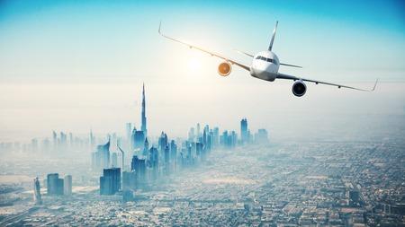 近代的な高層ビル都市上空を飛ぶ旅客機
