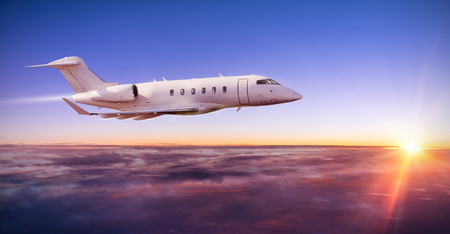 Private jet plane flying above clouds in dramatic sunset light Stock Photo