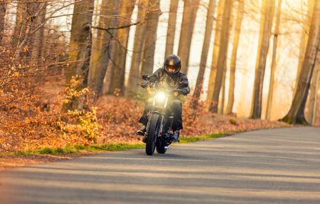 biker man: Young man riding black chopper on road in forest