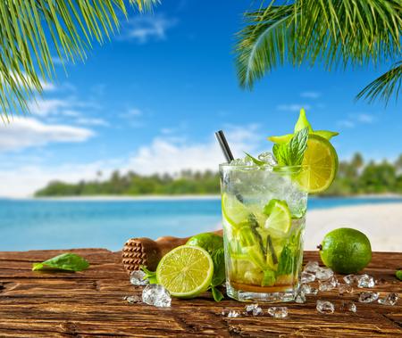 De drank van de zomermojito met onduidelijk beeldstrand op achtergrond